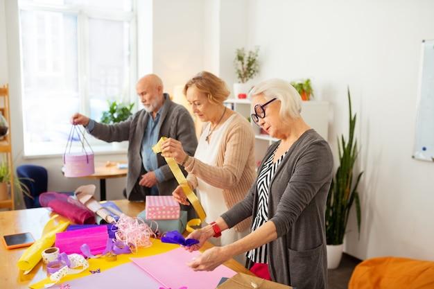 Processo criativo. pessoas simpáticas e seniores em pé à mesa enquanto usam o papel de embrulho