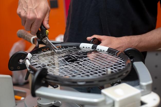 Processo de amarrar uma raquete de tênis em uma loja de tênis, conceito de esporte e lazer