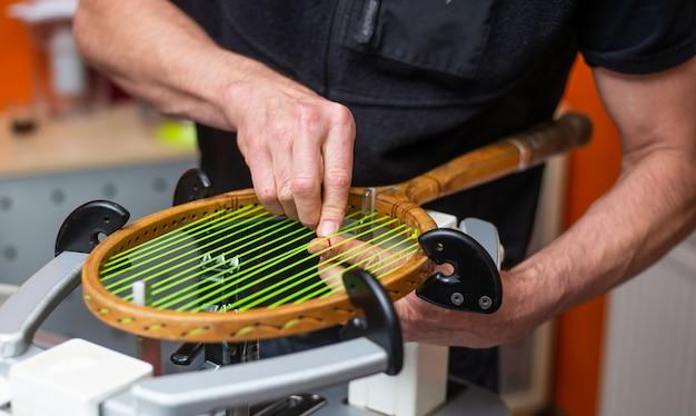 Processo de amarrar uma raquete de tênis histórica ou retro em uma loja de tênis, conceito de esporte e lazer