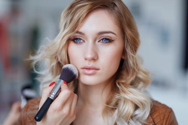 Processo de aplicação de maquiagem no rosto da mulher, closeup