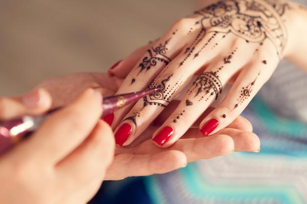 Processo de aplicação de mehndi nas mãos femininas