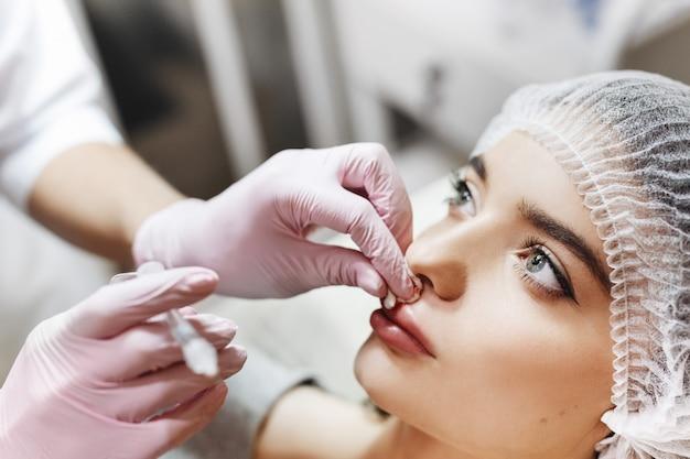 Processo de aprimoramento dos lábios. cosmetician faz uma injeção de ácido hialurônico nos lábios bonitos. a jovem garota com um rosto bonito no chapéu especial e mãos do médico nas luvas rosa.