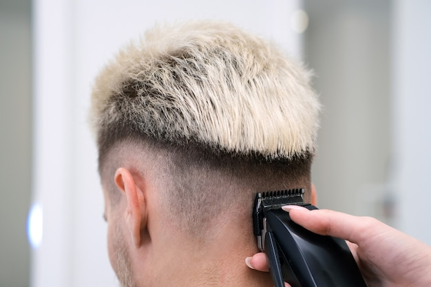 Processo de corte de cabelo de jovem loiro com aparador de cabelo em poltrona em salão de barbearia, conceito de barbearia para homens e meninos