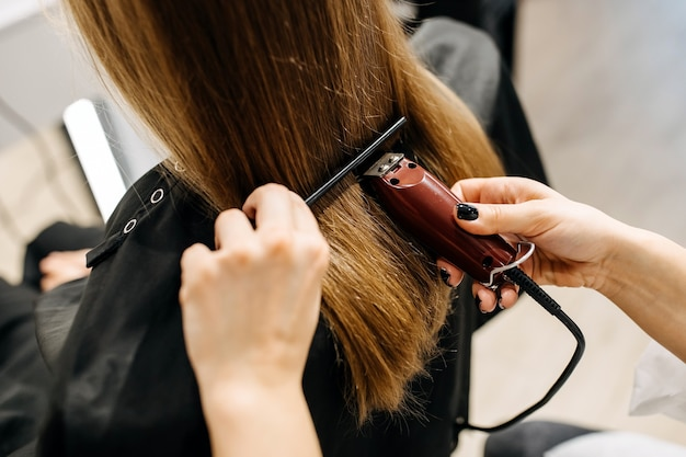 Processo de corte de cabelo em salão de beleza, usando máquina de cortar cabelo