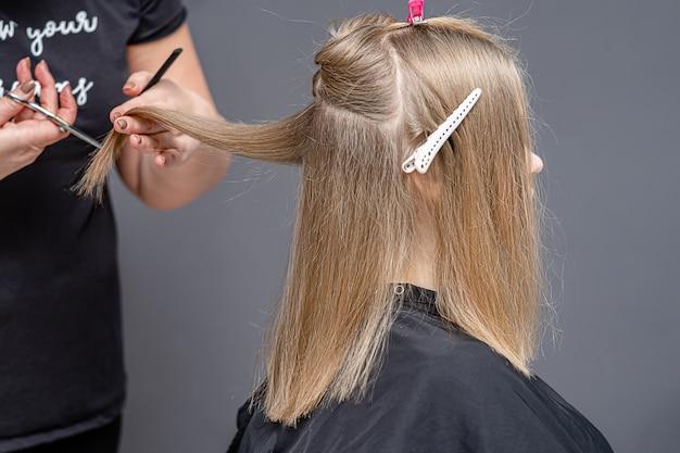 Processo de corte de cabelo feminino para jovem em um salão de cabeleireiro.