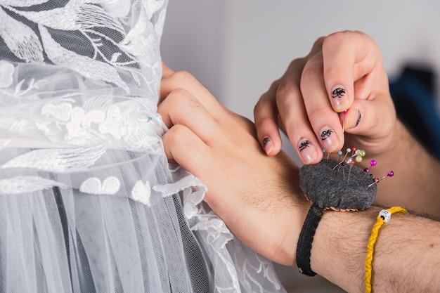 Processo de costura com manequim, agulha e renda - a mão do alfaiate trabalhando com manequim e tecido rendado.