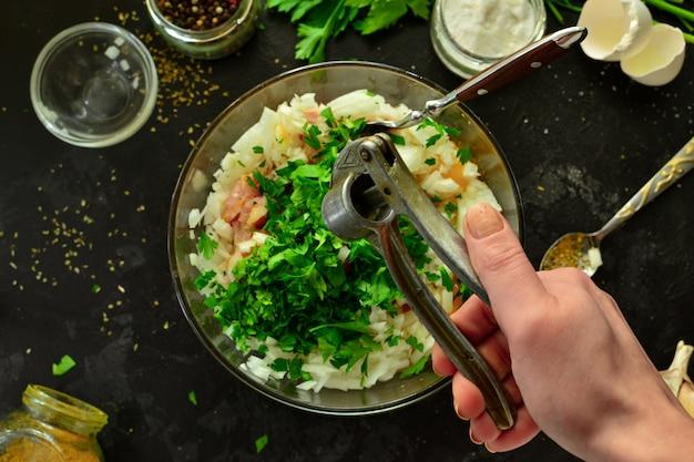 Processo de cozimento. carne picada e ingredientes, sal, pimenta, temperos, cebola, ovos, salsa, misture os ingredientes com uma colher. uma mulher está preparando frango picado para almôndegas. vista do topo.
