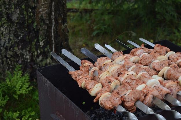 Processo de cozimento de carne de porco assada shish kebab ou shashlik em espetos de churrasco