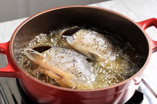 Processo de cozimento em casa, close-up cozinhando peixe frito com muito óleo usando panela vermelha.