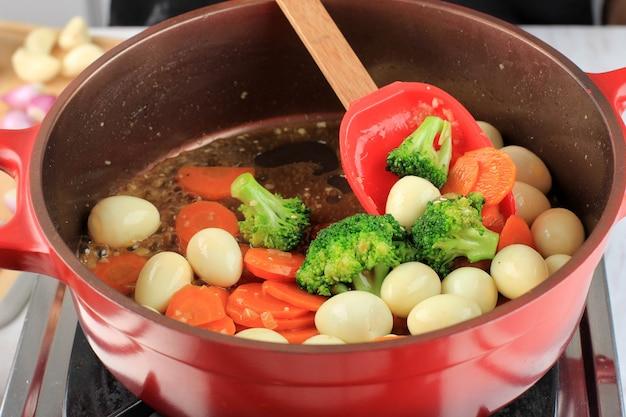 Processo de cozimento na cozinha processando panela vermelha, vegetais fritos e ovo de codorna com molho de ostra (telur puyuh saus tiram). mão de mulher mexa vegetais e ovo de codorna em uma panela