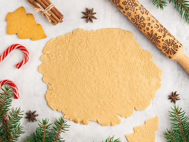 Processo de cozimento tradicional sobremesa de natal e ano novo, biscoitos de gengibre, rolo com padrão de flocos de neve, estrelas de anis e canela