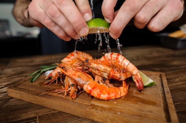 Processo de cozinhar saborosos camarões com suco de limão