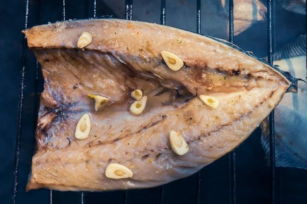 Processo de defumação de peixes. cavala defumada na grelha. close up smoking. vista de cima