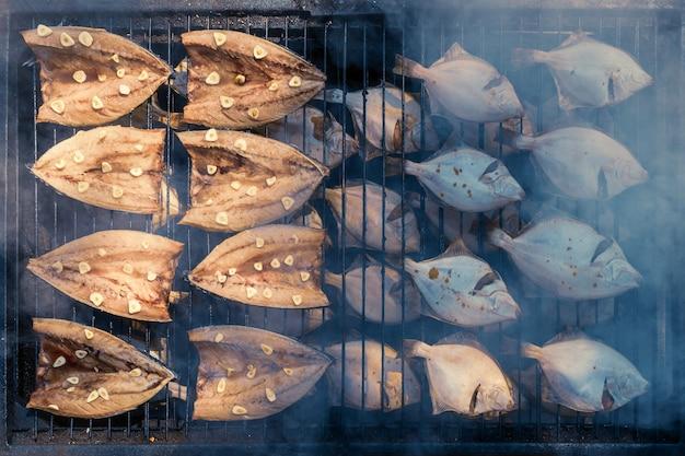 Processo de defumação de peixes. cavala e linguado defumados. close up smoking. veiw de cima