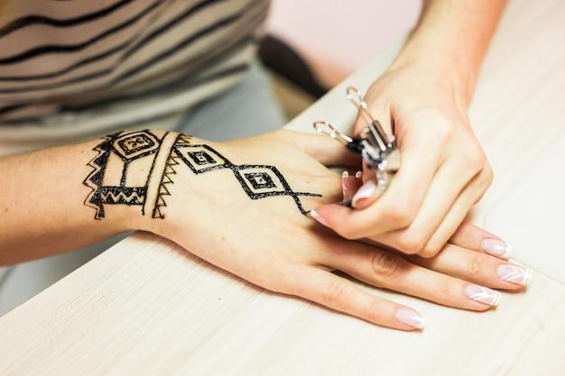 Processo de desenho do ornamento menhdi do henna na mão da mulher.