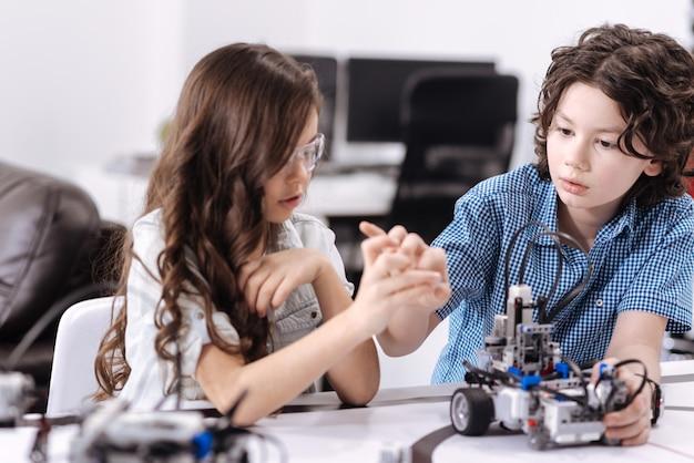 Processo de discussão. alunos curiosos, inventivos e habilidosos, sentados na escola e dando aulas de ciências, enquanto expressam curiosidade e trabalham com o robô