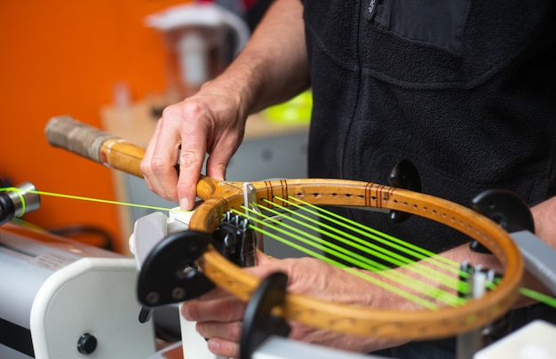 Processo de enfileiramento de uma raquete de tênis em uma loja de tênis, conceito de esporte e lazer, manutenção e tunning de raquete de tênis