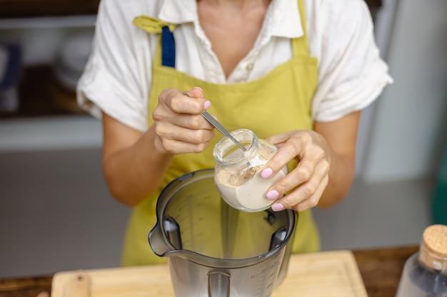 Processo de fabricação de pudim de chia de café da manhã saudável. mulher mistura sementes de chia, leite de amêndoa e extrato de fruta do dragão de cor natural rosa no liquidificador.