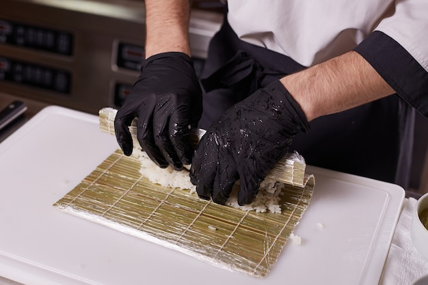 Processo de fabricação de sushi e rolos na cozinha do restaurante. chefs mãos com faca.