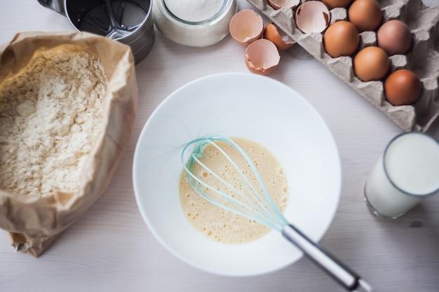 Processo de fazer a massa, a mão da mulher chicoteia ovos e farinha na tigela