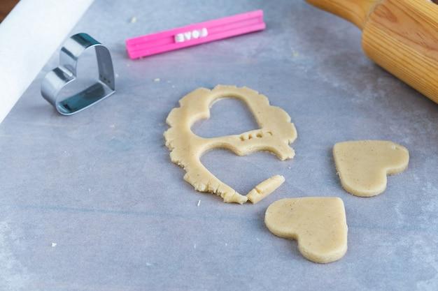 Processo de fazer biscoitos em forma de coração. conceito de pastelaria romântica.
