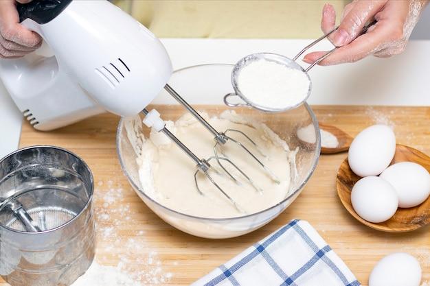 Processo de fazer massa para panquecas com ingredientes em uma mesa leve, os ovos e a farinha são batidos na batedeira