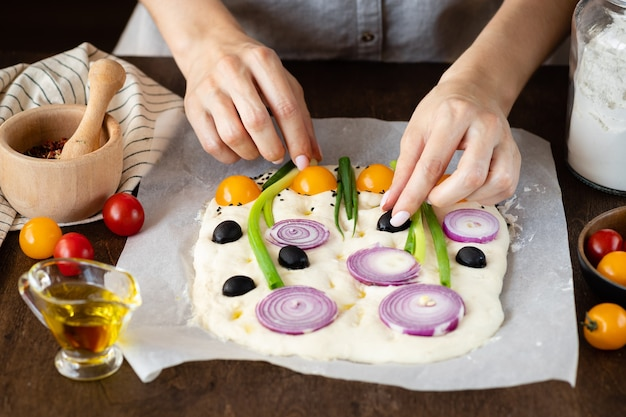 Processo de fazer pão italiano com as mãos das pessoas da arte focaccia decorando a massa de focaccia crua