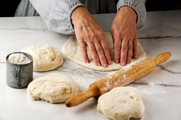 Processo de fazer pizza, mão de mulher trabalhando com massa e farinha