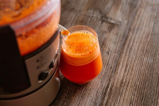 Processo de fazer suco em um espremedor de sumos, processo de preparação de suco fresco em sumo, suco de cenoura