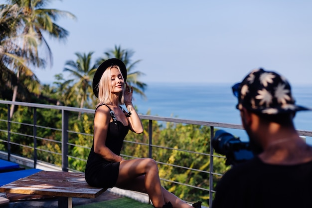Processo de filmagem de vídeo homem faz um vídeo na câmera profissional de uma jovem blogueira elegante em uma vista tropical de férias