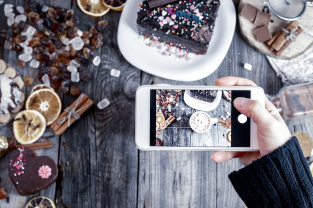 Processo de fotografar a mesa do smartphone com comida e bebida