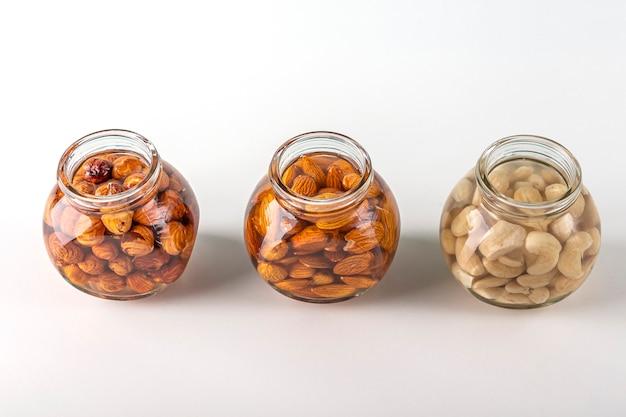 Processo de imersão de várias nozes, amêndoas, avelãs e caju em água em frasco de vidro para ativar