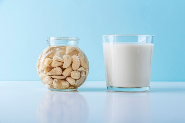 Processo de imersão de várias nozes: avelãs em água para ativar e copo de leite vegetal