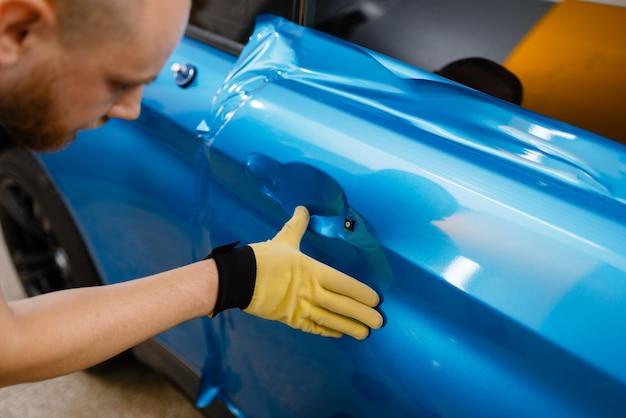Processo de instalação de película protetora de vinil ou filme, embalagem de carro. trabalhador faz detalhamento de automóveis