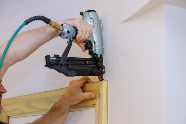Processo de instalação na moldura da moldura pregando as molduras das portas