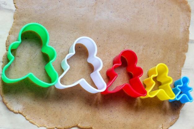 Processo de lidar com biscoitos homem de gengibre, use massa de pão de gengibre de corte de molde de homem de gengibre vermelho no papel manteiga ao redor de cortadores de biscoito coloridos na mesa de madeira branca. vista do topo