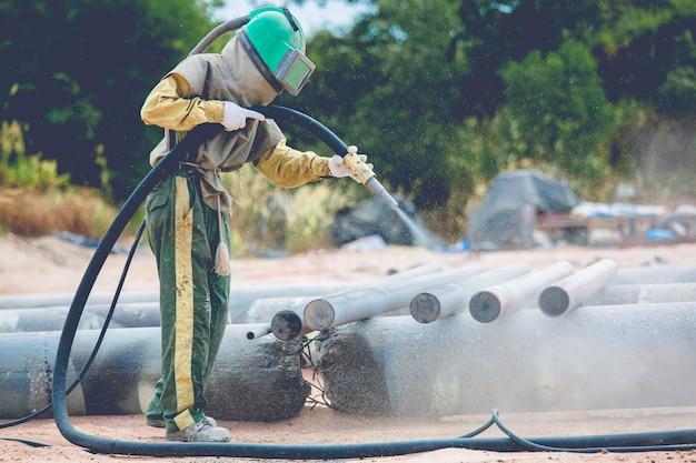 Processo de limpeza de poeira do trabalhador masculino com jato de areia, superfície do duto de aço antes de pintar na fábrica