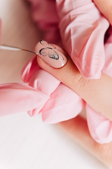 Processo de manicure desenhando uma borboleta desenhando na unha com um pincel fino.