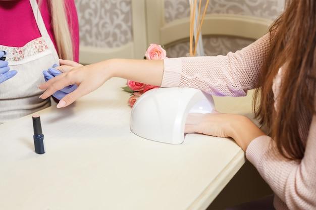 Processo de manicure. lâmpada manicure profissional