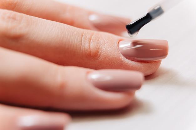 Processo de manicure. o manicure pinta as unhas. lixador de unha.