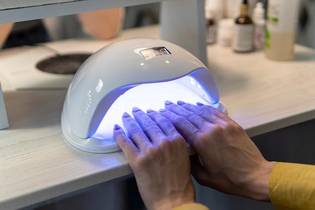 Processo de manicure polonês com lâmpada uv. uma mulher seca as unhas em casa. procedimento de salão.