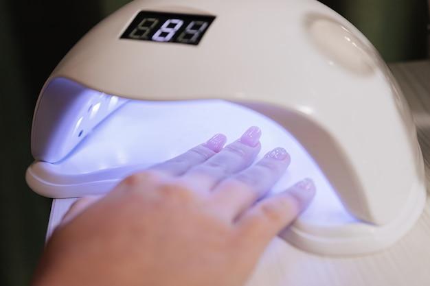 Processo de manicure. secagem de unhas em aparelho com lâmpadas ultravioleta.