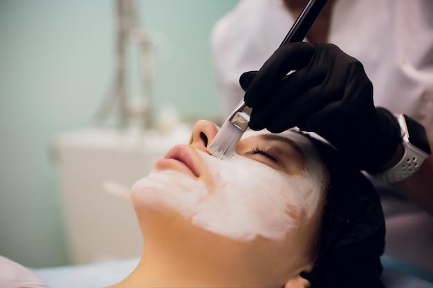 Processo de massagem de máscara cosmética e tratamentos faciais no salão de beleza