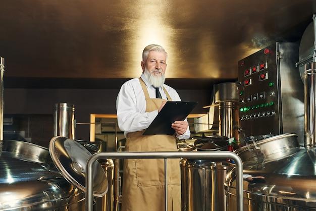 Processo de monitoramento de trabalhador de cervejaria profissional de fabricação de cerveja. trabalhador bonito, idoso e barbudo, vestindo avental segurando uma pasta, olhando para a câmera.