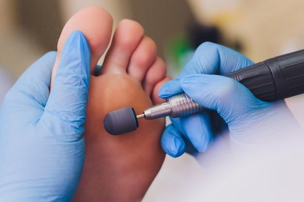 Processo de pedicure close-up, polimento de pés, pessoas irreconhecíveis. rosto borrado.