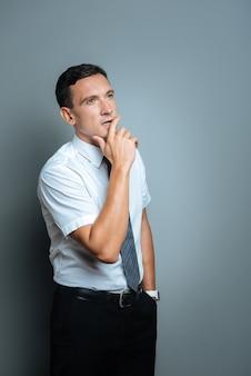 Processo de pensamento. homem jovem e atencioso colocando a mão no bolso e segurando seu queixo enquanto pensa em seu trabalho