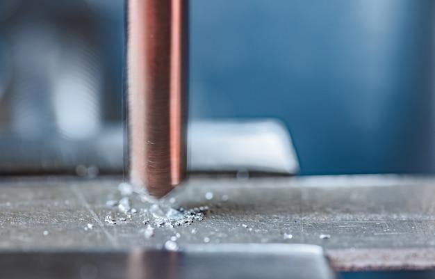 Processo de perfuração com close-up de aparas, máquina de perfuração no local de trabalho de um serralheiro