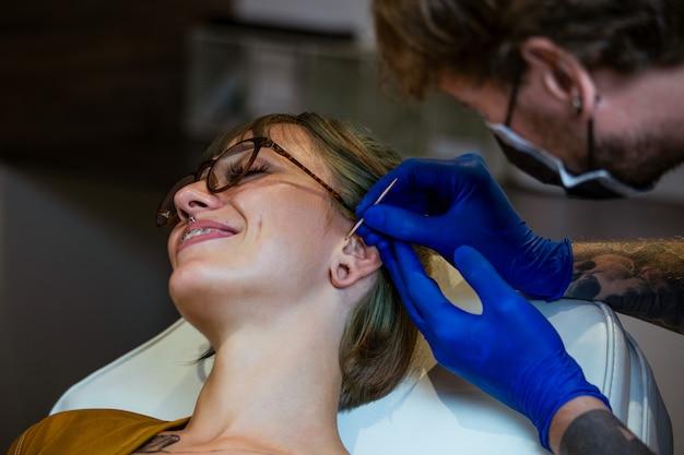 Processo de piercing na orelha com luvas esterilizadas de neadle e látex. procedimento para piercing na orelha