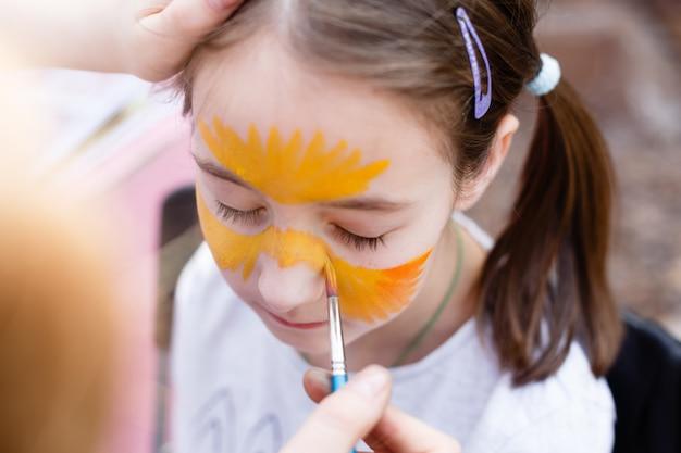 Processo de pintura infantil no rosto da menina