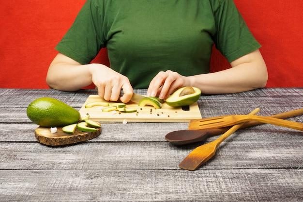 Processo de preparação de alimentos saudáveis a menina corta um abacate com uma faca